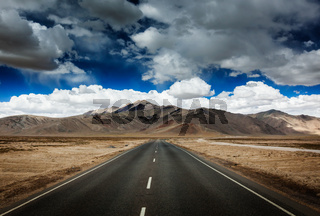Travel forward concept background - road on plains in Himalayas with mountains and dramatic clouds. Manali-Leh road