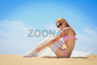 beautiful woman with white sarong sitting on thel beach
