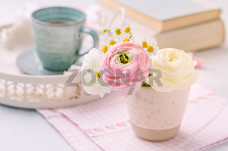 Beautiful tender blossoming of fresh cut bouquet with cup of tea nad books in background on kitchen table