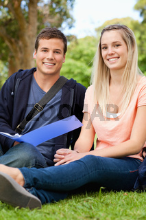 Portrait of a smiling tutor helping a teenager to revise
