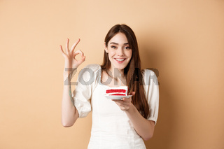 Happy birthday girl show okay gesture and hold bday cake, making wish on her holiday, standing on beige background