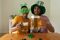 Smiling mixed race gay male couple wearing st patrick's day costumes and raising glasses of beer