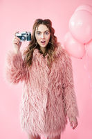 Portrait of young amazed woman taking photo with retro camera on pink background