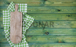 Cutting board on green checkered tablecloth, top view