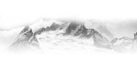 Black and white panorama of winter snowy high mountains in fog