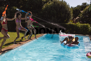 Diverse group of friends having fun playing with water guns at a pool party