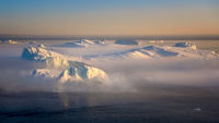 floating glaciers at fjord Disco Bay West Greenland with fog