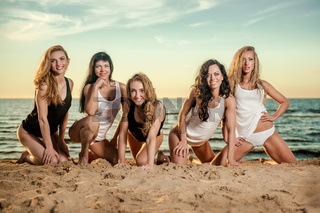 Five beautiful and sexy ladies posing on the beach at sunset
