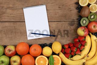 Früchte auf einem Holzbrett mit Notizblock