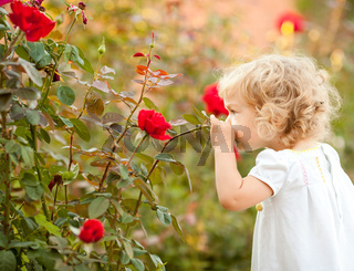 Beautiful child smelling rose
