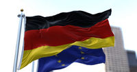 The national flag of Germany waving in the wind together with the European Union flag blurred in the background