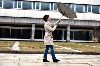 Woman with umbrella in windy weather