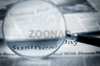 Loupe lies on the newspaper with title Business day