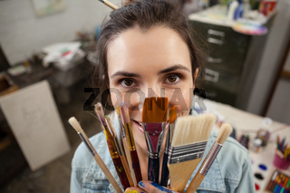 Woman holding various brushes in drawing class