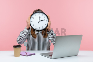 Emotional young woman sitting and working on office with pink background.