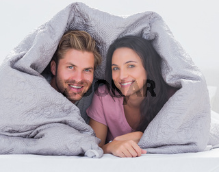 Cheerful couple wrapped in the duvet