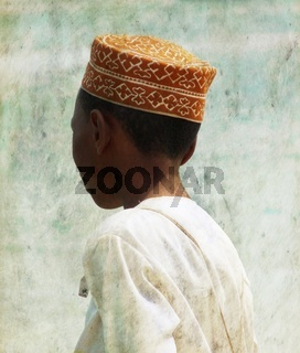 Close up of young boy in traditional clothes from behind, Zanzibar