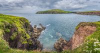 Large panorama with Dingle Lighthouse and bay surrounded by cliffs