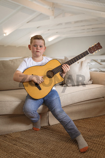 Portrait of caucasian boy playing guitar sitting on the couch at home