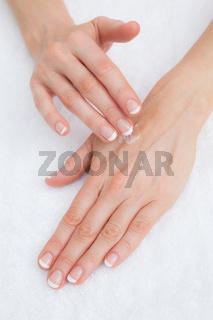 Woman applying cream on hand