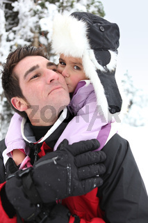 Father giving daughter piggy-back in the snow
