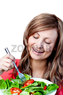 Cute woman is eating a salad