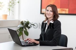 Junge, attraktive Geschäftsfrau sitzt am Laptop