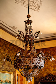 Antique massive metal chandelier with bulbs in the castle.