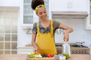 Mixed race woman making a healthy drink and smiling in a kitchen