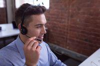 Caucasian businessman wearing phone headset sitting at desk using computer