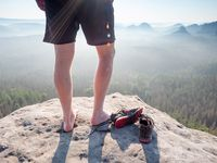 Middle age healthy male body with naked legs on mountain peak rock