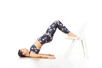 Young sporty attractive woman in bright white yoga studio, stretching and relaxing during restorative yoga using white chair as a gadget. Healthy active lifestyle