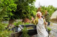 Ältere Frau als Gärtnerin singt aus Spaß in einen Schlauch