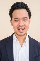 Portrait of Asian businessman wearing suit against plain background while smiling