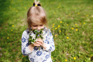 Little girl sniffing spring flowers on green lawn in the garden