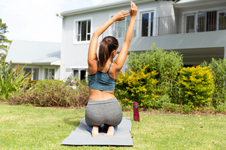 Caucasian woman exercising practicing yoga in garden