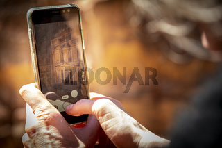 Tourist taking a picture with a smartphone, or mobile phone of The Treasury from the viewpoint in Petra, near Wadi Musa, Jordan