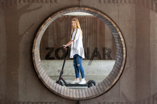 Casual caucasian teenager riding urban electric scooter in urban environment. Urban mobility concept