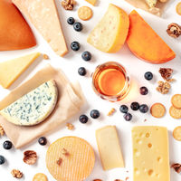 Cheese and wine tasting and pairing flat lay on a white background. Many different cheeses, overhead square shot