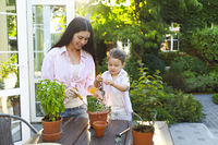 Mother with little daughter having fun and planting flowers in pot with soil together,