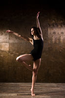 young girl dancer with long hair in black clothes, gymnastic swimsuit, in a dancing pose passe on the toe and hands up on a wooden floor with a dark background. Dance theme Contemporary and Classical