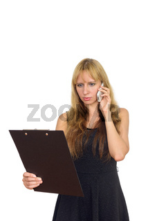 Portrait of blonde businesswoman talking on the phone and reading on clipboard
