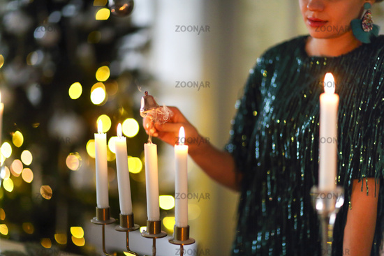 Crop stylish woman extinguishing candles after New Year party