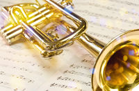 Golden trumpet on sheet music with scenic reflections and lens flare