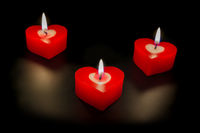 Heart shaped candles on black background