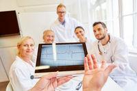 Ärzte mit EKG auf Tablet Computer