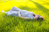 Pregnant woman resting on lawn