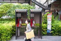 Singapur, Republik Singapur, Frau mit Mundschutz geht an Telefonzellen vorbei