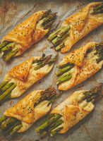 Baked green asparagus in puff pastry sprinkled with sesame seeds. Placed on a white baking paper