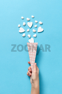 Paper cone with small hearts in woman's hand.